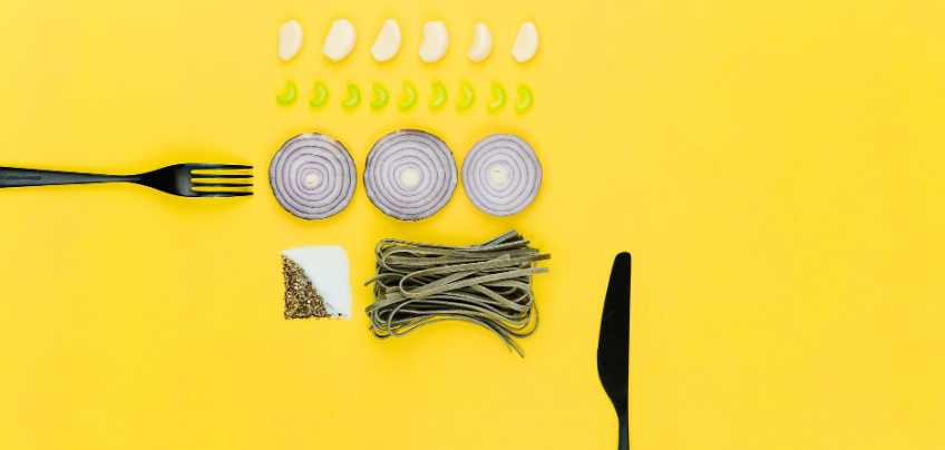 knife, fork and different food ingredients on a yellow surface